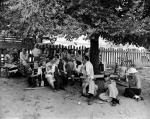 Short Creek raid, Arizona, 1953. As arraignments of the adults drag on in Short Creek's schoolhouse, transformed by the authorities into a temporary site for pre-trial hearings, a group of children and women wait in the schoolyard with state police guarding them.