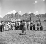 Under an officer's supervision, arrested polygamists line up beneath jagged Arizona cliffs, 1953.