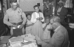 Two girls stand with their mother as she is questioned by an officer and Arizona Attorney General Ross Jones (seated) after the 1953 Short Creek raid.